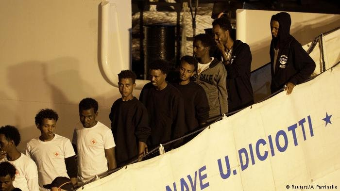 A stream of migrants disembark from the Diciotti, an Italian coast guard boat