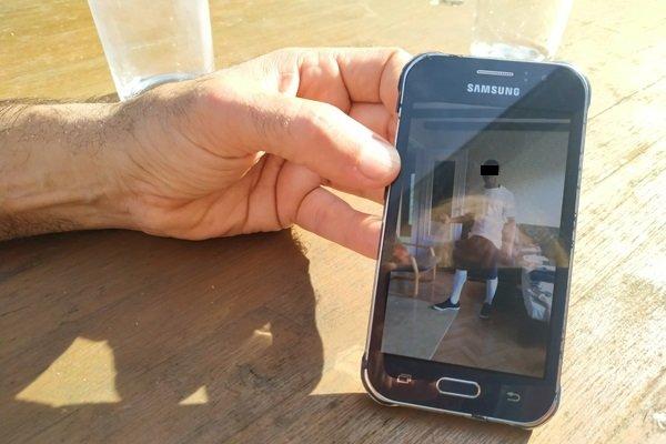 Sur son portable, Frédéric a toujours la photo de Zachée posant en tenue de foot. Crédit : Alcyone Wemaëre