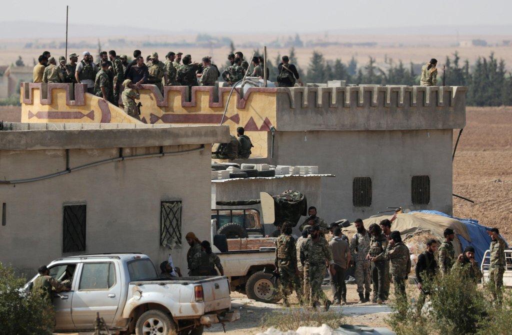 رويترز |مجموعة من المقاتلين السوريين المدعومين من تركيا يجتمعون بالقرب من بلدة تل أبيض الحدودية، سوريا، 22 أكتوبر/ تشرين الأول 2019.