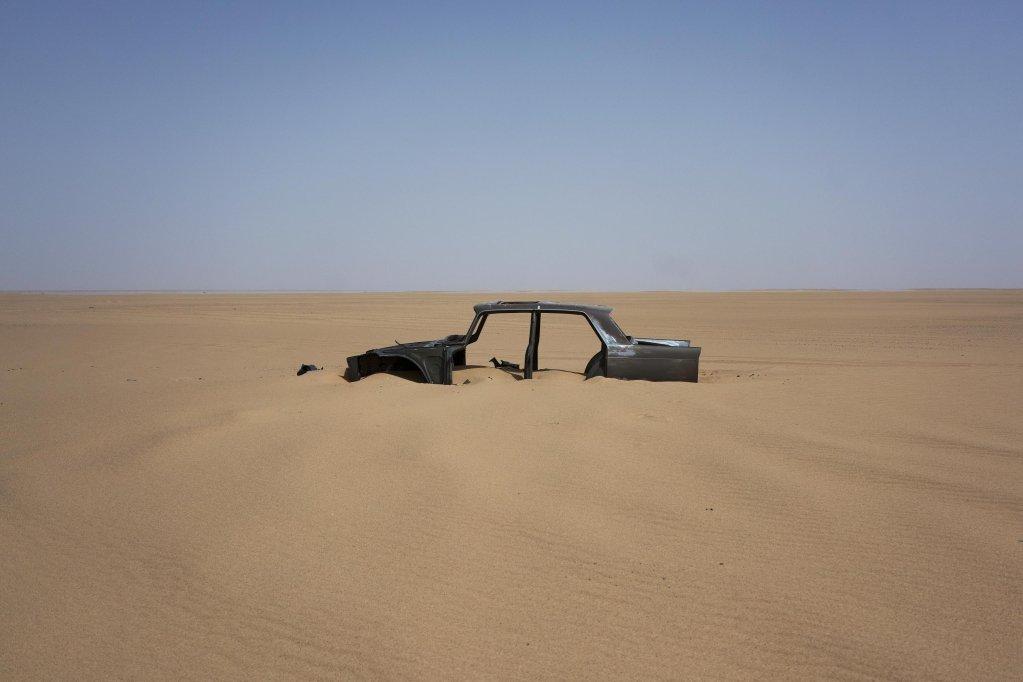 ANSA / بقايا سيارة مهجورة في منطقة تينير الصحراوية في النيجر، التي يمر بها طريق سريع يبلغ طوله 4500 كيلو متر، وهو أيضا الطريق المفضل للمهاجرين المتجهين نحو الشمال. المصدر: أنسا/ إيه بي/ جيرمو ديلاي.