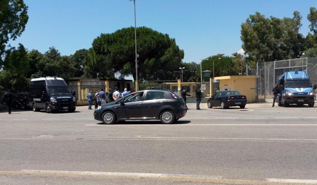 """ANSA / أفراد الشرطة أمام مركز """"إيزولا كابو ريسوتو"""" في مدينة كروتوني الإيطالية. المصدر: أنسا / كليمنتي أنجوتي."""