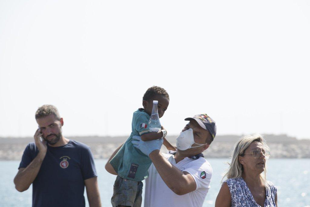 نساء وأطفال مهاجرون يتم مساعدتهم من قبل فريق طبي وضباط إنفاذ القانون بعد هبوطهم من إحدى سفن حرس السواحل الإيطالي في ميناء بوزالو بصقلية خلال يوم الأحد الماضي. المصدر: أنسا/ فرانشيسكو روتا.