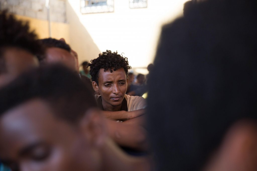 Migrants sit at the Njila detention center in Tripoli, Libya.Credit: EPA/STR