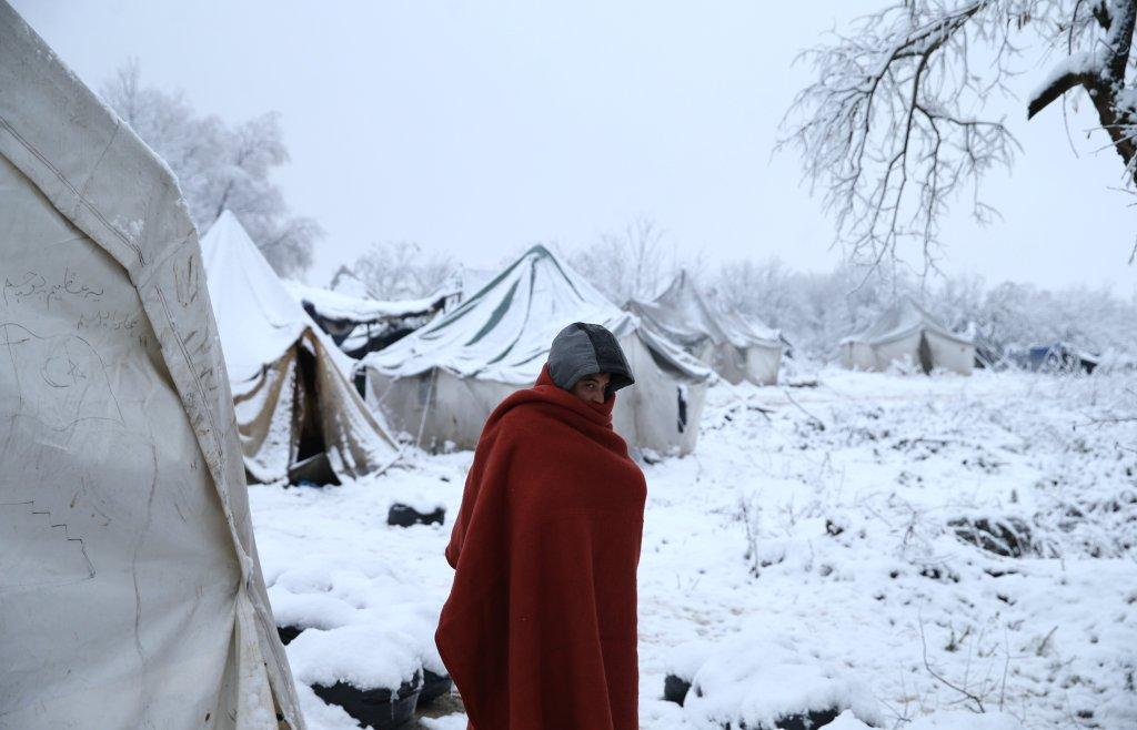 Un homme se réchauffe à l'aide d'une couverture dans le camp de Vucjak où les migrants n'ont aucun accès à l'eau ou au chauffage. Crédit : Reuters