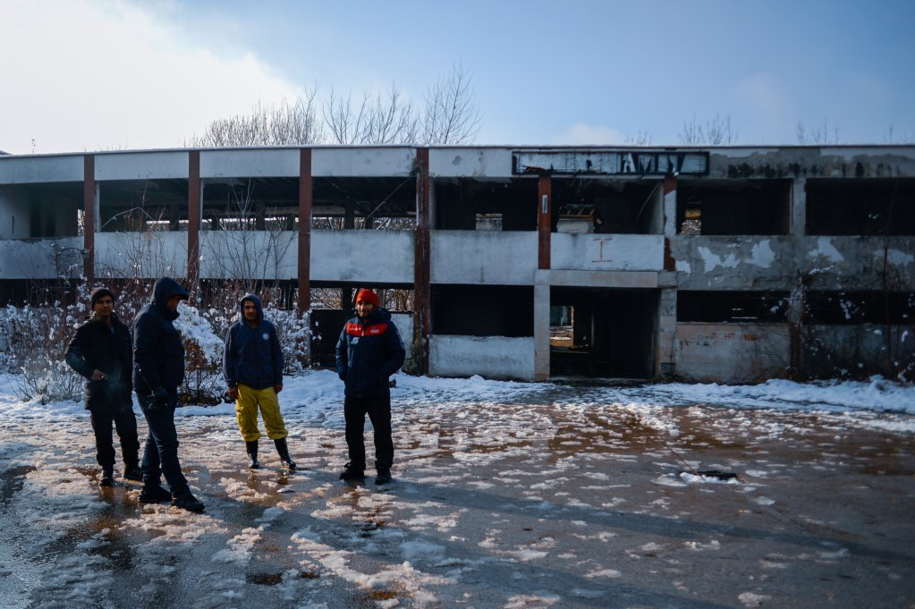 Migrants stand outside the defunct Krajina Metal factory in Bihac, February 2021 | Photo: Kemal Softic
