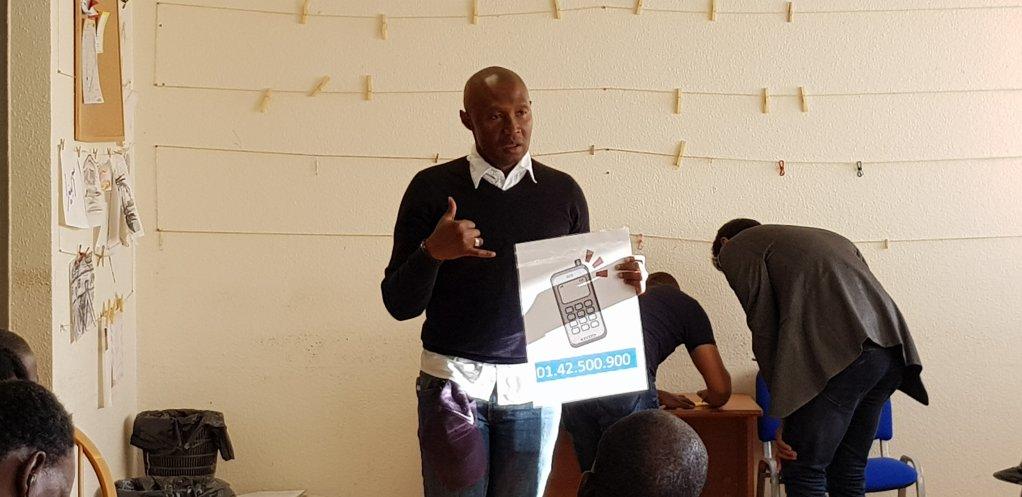 Charles-Patrick, bénévole ivoirien au CEDRE, explique la procédure d'asile à de nouveaux arrivants. Crédit : Anne-Diandra Louarn / InfoMigrants