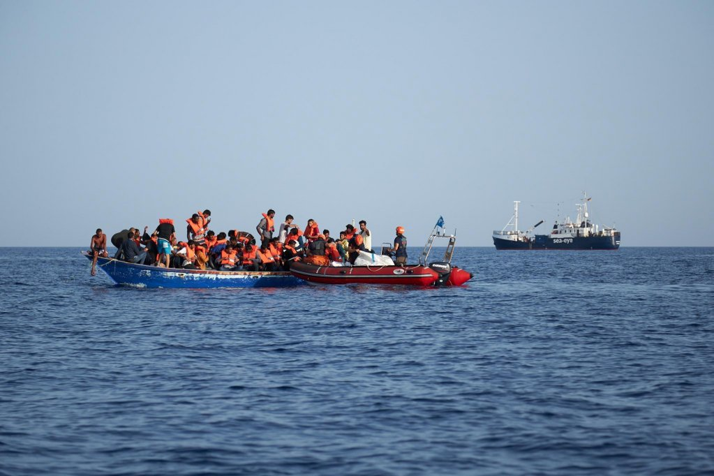 A handout photo made available by German civil sea rescue organization Sea-eye shows a boat carrying migrants (l) and a rescue boat of Sea-eye, in the Mediterranean sea | Photo: SEA-EYE