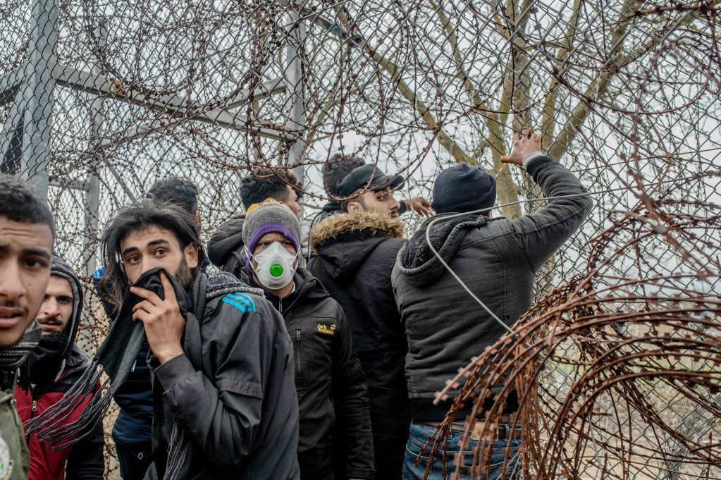 Migrants in the buffer zone at the Turkey-Greece border try to remove fences during clashes with Greek police, after attempting to cross into Greece from Turkey, near the Pazarkule crossing in Edirne, Turkey, on March 4, 2020 | Photo: BULENT KILIC/AFP
