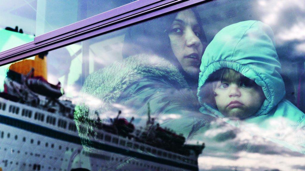 © Louisa Gouliamaki, AFP |Dans le bus qui les conduit vers un centre d'hébergement, une mère et son enfant regardent le paquebot affrété par le gouvernement grec pour les transporter au Pirée en réponse à l'aggravation de la situation dans les îles grecques de Kos, Lesbos et Chios, en 2015.