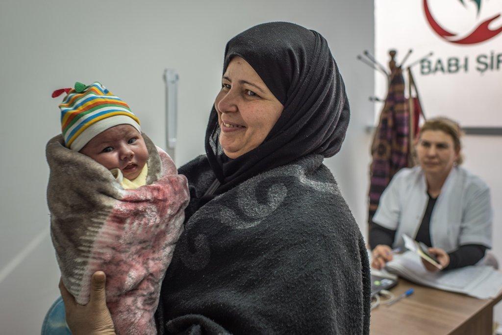 رانيا الجص تحمل أحد أحفادها في مركز صحي مخصص للاجئين السوريين في أنقرة