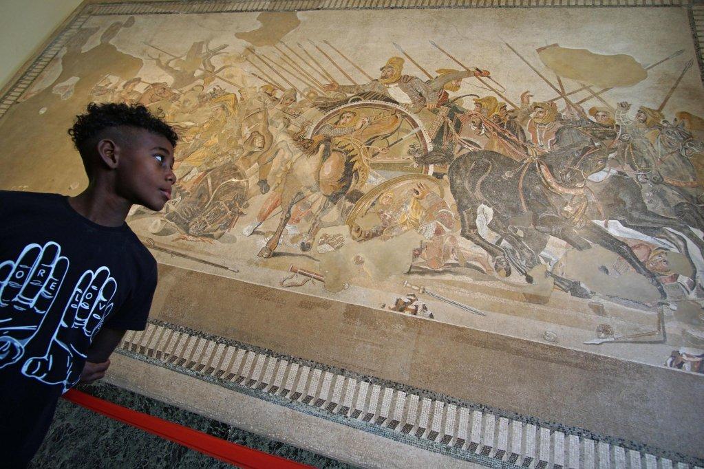 ANSA / شاب مهاجر يبدي إعجابه بلوحة جدارية في المتحف الوطني للآثار في نابولي، خلال يوم مخصص للمهاجرين واللاجئين. المصدر: أنسا / سيزار أباتي.