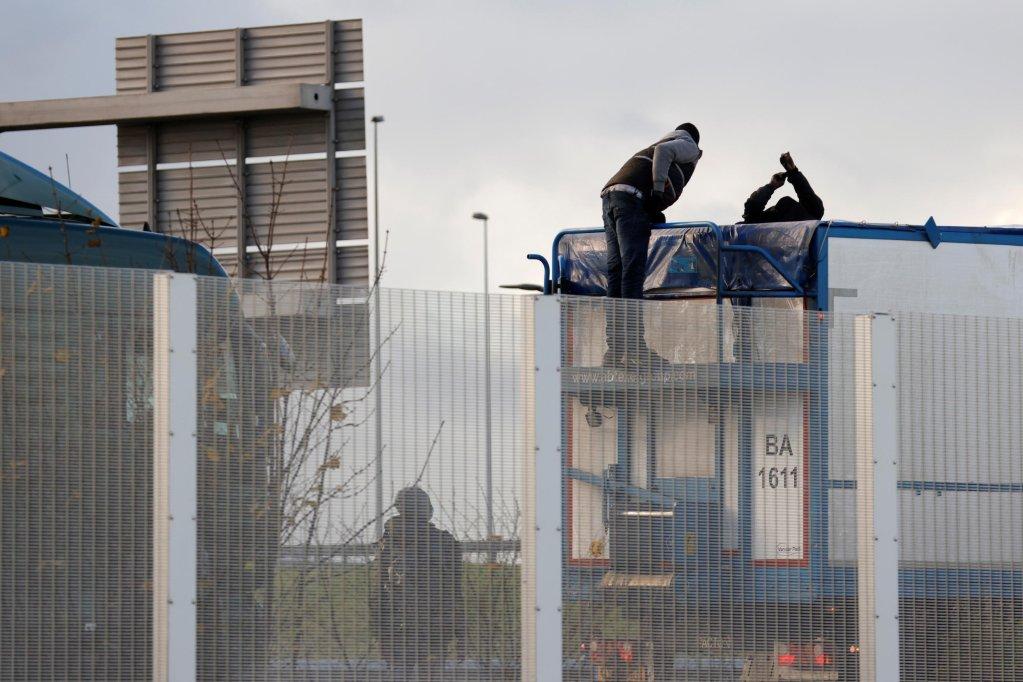 REUTERS - PASCAL ROSSIGNOL |Des migrants montent à bord d'un camion sur l'autoroute A16 qui mène au tunnel sous la Manche, près de Calais. Le 17 décembre 2020.