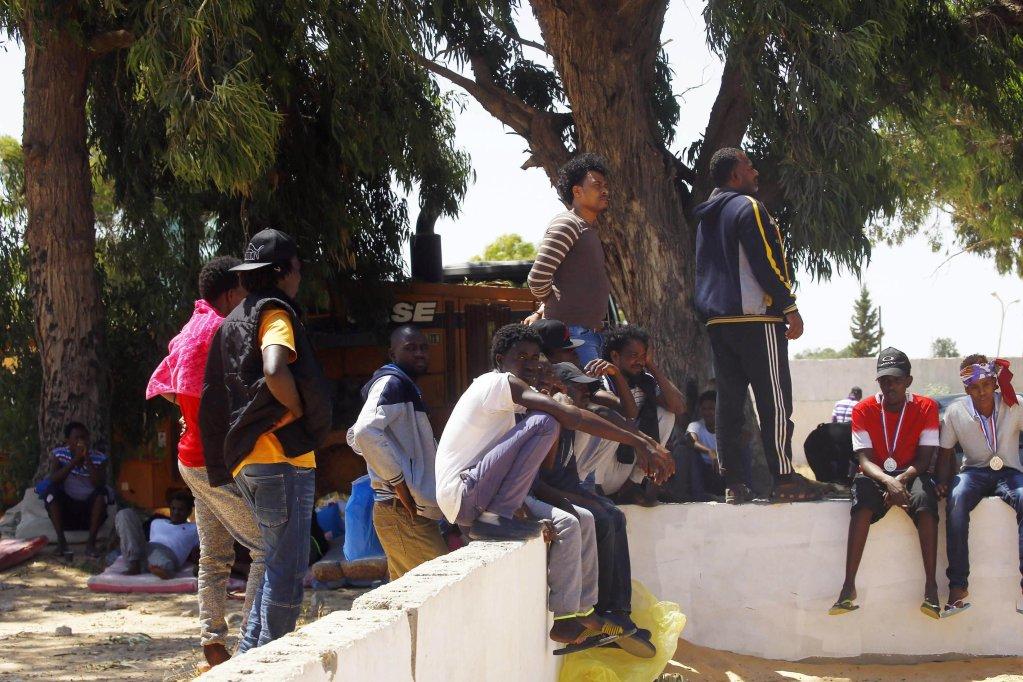 ANSA / مهاجرون يجلسون بالقرب من مركز تاجوراء المدمر جراء غارة جوية في العاصمة الليبية طرابلس. المصدر: إي بي إيه.
