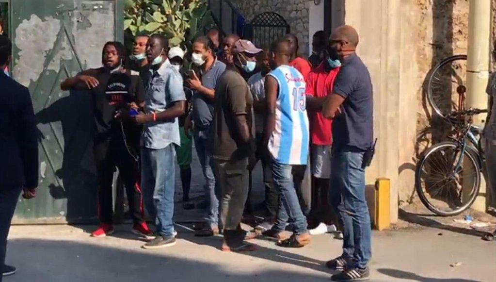 مهاجرون من ضيوف إرسالية مجتمع بياجيو كونتي في باليرمو أمام بوابة الدخول، وبينهم 37 أصيبوا بكورونا في أيلول/ سبتمبر الماضي. المصدر: أنسا/ إجناسيو ماركيزا.