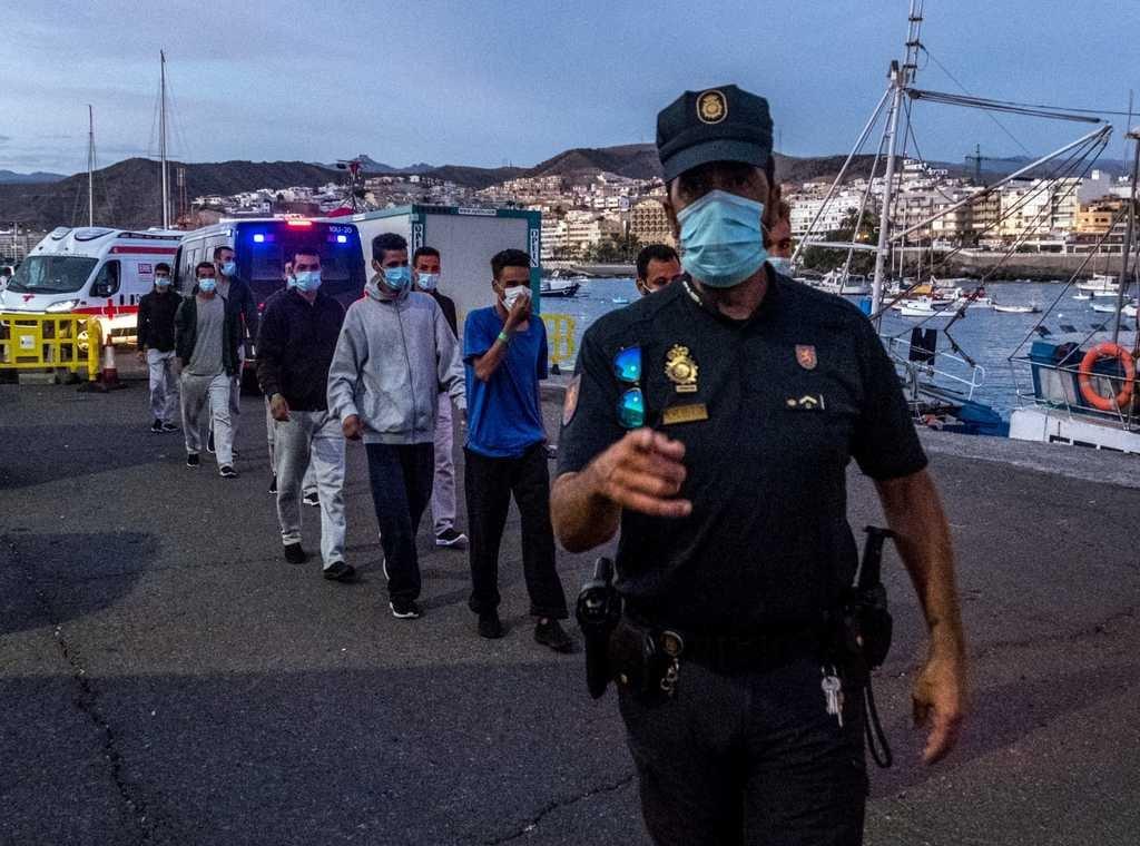 شرطي يقود مهاجرين واصلين حديثا الى المخيم في ميناء أرغينيغين. الصورة لخافيير بولوز/مهاجر نيوز