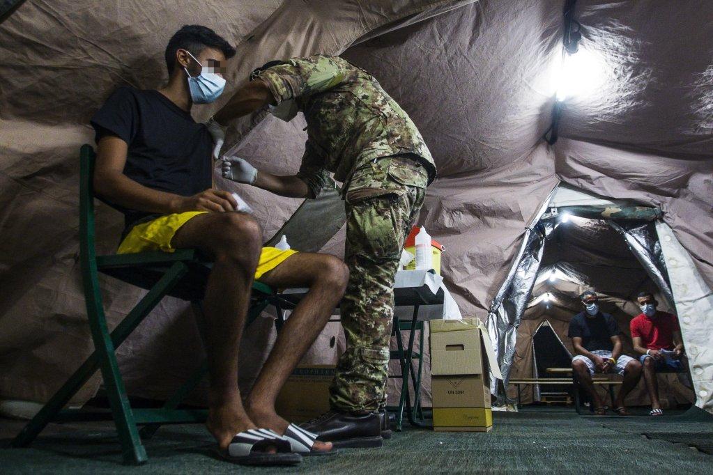 عناصر من الجيش الإيطالي خلال عملية تطعيم المهاجرين الذين وصلوا إلى لامبيدوزا. المصدر: أنسا/ أنجيليو كاركوني