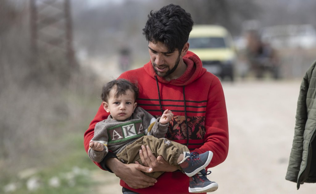 A migrant man and his son walk near the Greek border at the Pazarkule crossing in Edirne, Turkey, 9 March 2020. Many of the migrants who gathered at the border are from Syria | Photo: EPA/TOLGA BOZOGLU