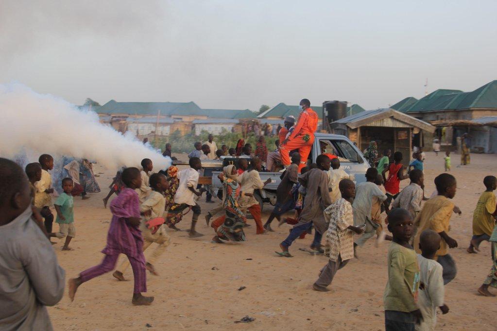 ANSA / أطفال يلعبون وهم يواكبون آلة تعقيم بتقنية التبخير مثبتة على متن شاحنة لتطهير مخيم مايدوجوري للنازحين في نيجيريا. المصدر: أودو مارتي / إيه أف بي.