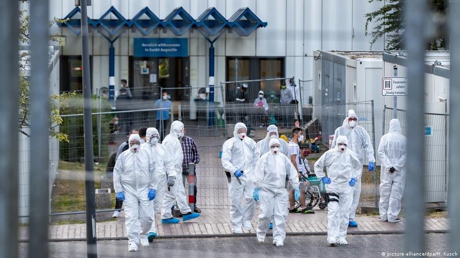 کارمندان امنیتی در یکی از اقامتگاه های مهاجرین در شهر بن آلمان که هفتاد درصد آن به ویروس مبتلا شده بودند (آرشیف)
