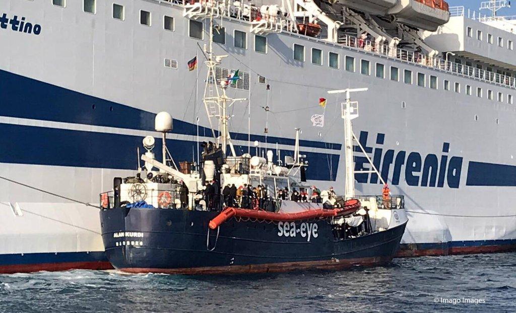سفينة آلان كردي راسية في ميناء باليريمو بجانب عبارة إيطالية كبيرة نقل إليها المهاجرون حيث تم وضعهم تحت الحجر الصحي