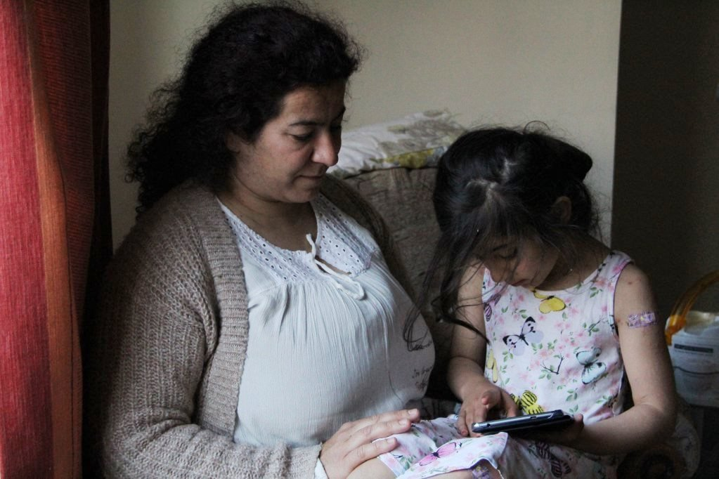 Hema sits with her daughter Jana in their new home in Stoke-on-Trent, England. In 2015 and 2016, the family made the journey to the UK from Iraq.  Credit : Brenna Daldorph