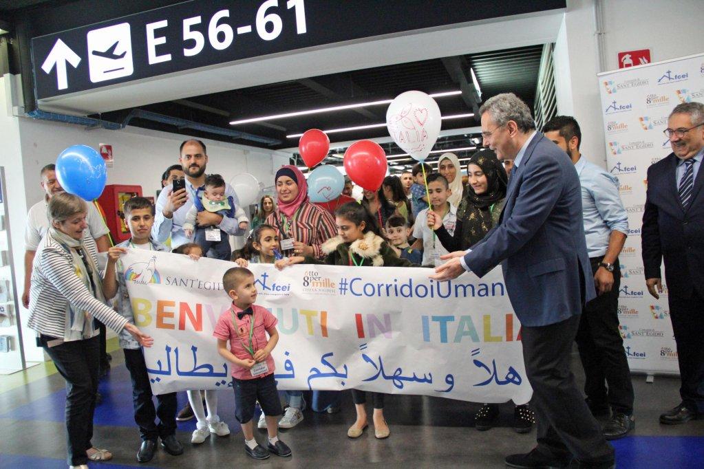 """ماركو إمبايلياتسو رئيس """"سانت إيجيديو"""" وهو يرحب بلاجئين سوريين في إيطاليا، في إطار مشروع تدعمه الجمعية. المصدر: أنسا."""