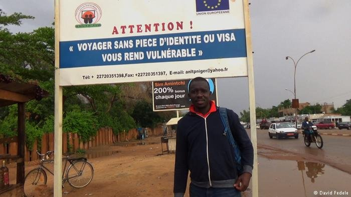 Kumut Imesh is standing in front of a big sign that reads in French: Attention! Voyager sans piece d'identite ou visa vous rend vulnérable | Photo: David Fedele