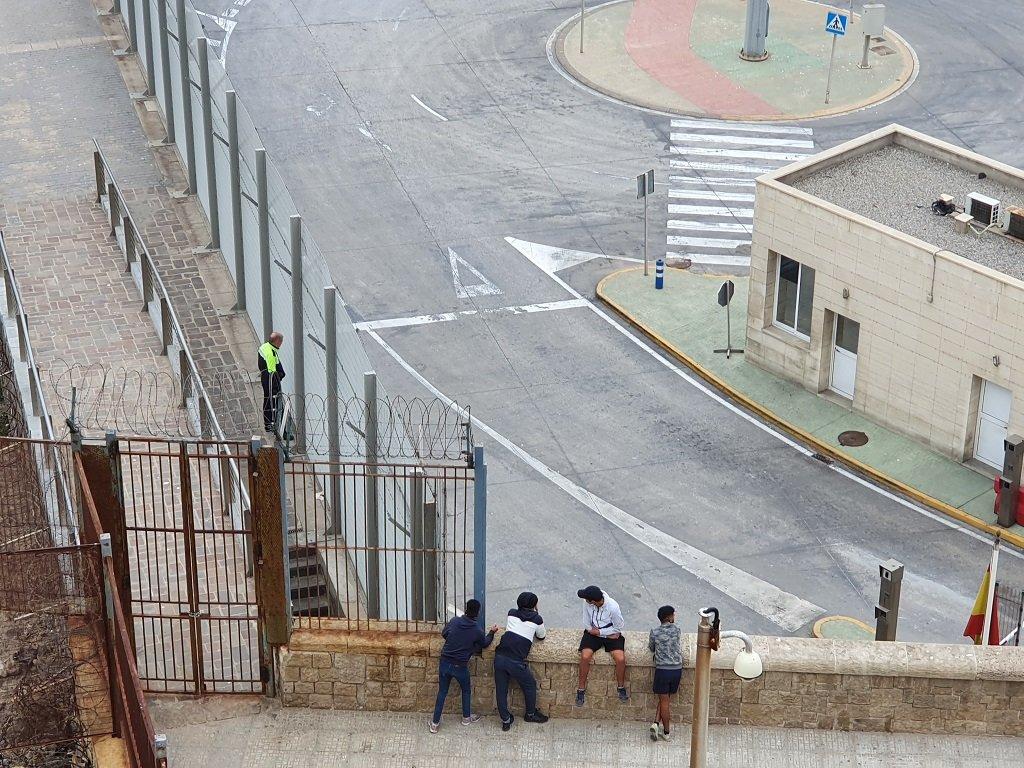 مهاجرون قاصرون يراقبون رجل أمن في ميناء مليلية، ينتظرون فرصة مناسبة للتسلل إلى رصيف الميناء، 20 أيار/مايو 2021. شريف بيبي/مهاجر نيوز