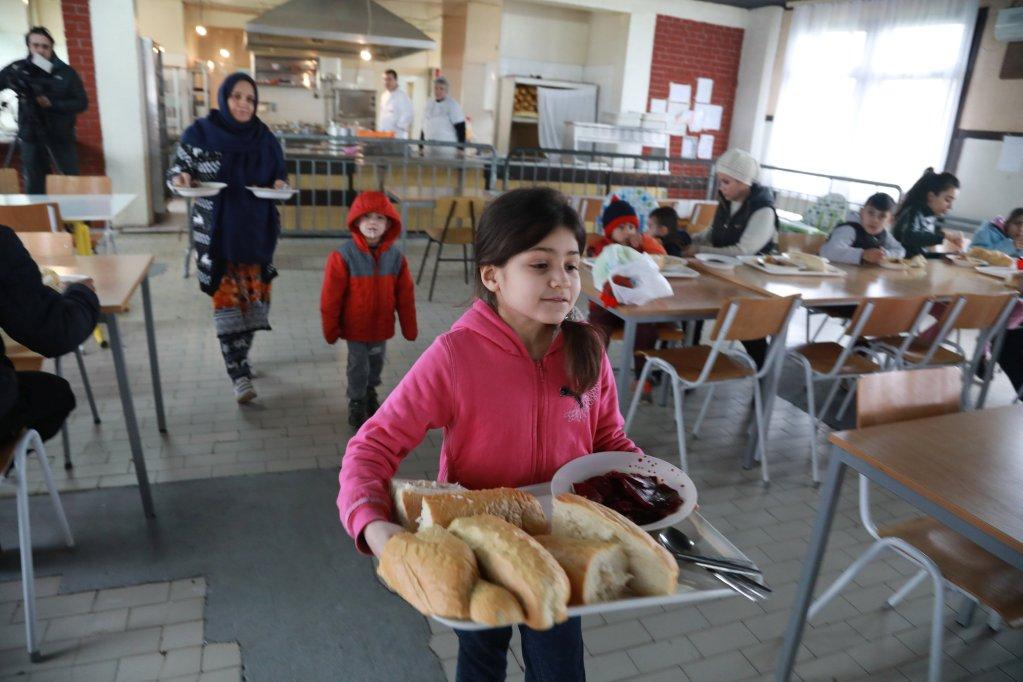 REUTERS/Djordje Kojadinovic |Une petite fille transporte de la nourriture dans le camp pour réfugiés et migrants de Krnjaca, en Serbie, le 16 janvier 2018.