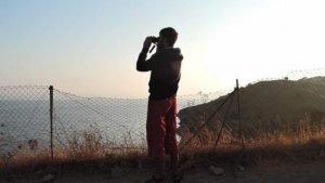 Un homme guette l'arrivée de migrants par la mer sur l'île de Lesbos. Crédit : Rutgert Verhaegen