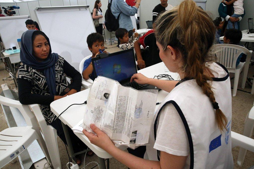 """ansa / عدد من المهاجرين يحضرون عملية التسجيل في مخيم للاجئين في أثينا. المصدر: صورة من الأرشيف من """"إي بي إيه""""."""