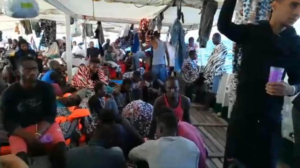 مهاجرون على متن السفينة أوبن آرمز ينتظرون لحظة رسو السفينة في ميناء لامبيدوزا. المصدر: أوبن آرمز