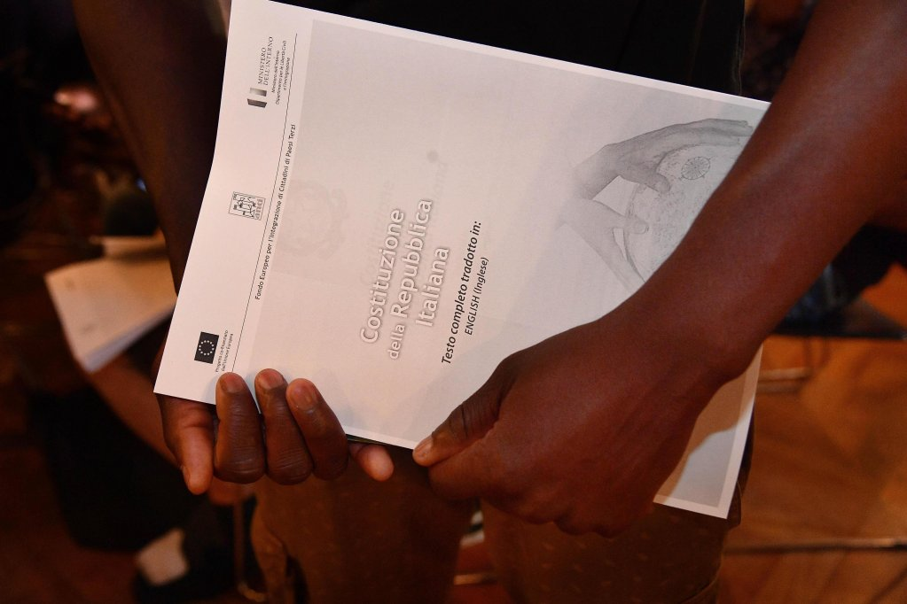 "Young migrants take a copy of the Italian Constitution translated in English, French and Arabic during the first ""Riconoscercsi"" course for migrants and asylum seekers in Genoa. Credit: ANSA/ Luca Zennaro"