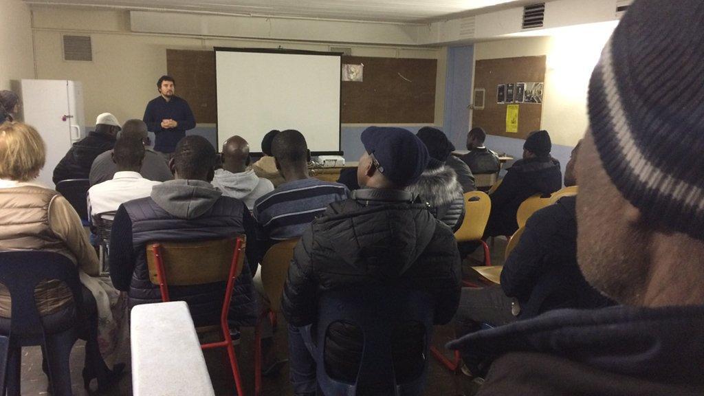"""Le réalisateur Jonathan Millet (au fond) devant les résidents du foyer Saint-Just, après la projection de son film """"Et toujours nous marcherons"""". Crédit : InfoMigrants"""