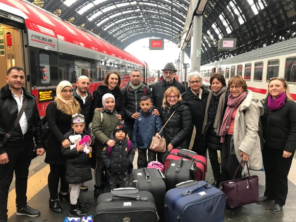 The Almohammad family, from Aleppo, Syria (on the left), is welcomed in Milan's central station by the vice-president of the Union of Italian Jewish Communities, Giorgio Mortara (center) | Photo: MOKED.IT