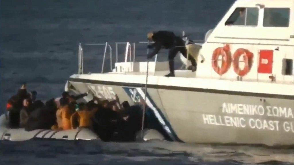 صورة مأخوذة من الفيديو تظهر أحد عناصر خفر السواحل اليوناني يضرب قاربا مطاطيا لمهاجرين بواسطة عصا طويلة، 2 آذار/مارس 2020