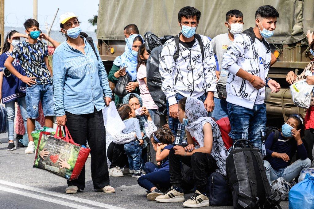 مهاجرون ينتظرون استقلال حافلة خارج مخيم كارا تيبي في طريقهم لميناء ميتيليني بجزيرة ليسبوس اليونانية. المصدر: إي بي إيه / فانجيليس بابا أنتونيس/ أنسا.