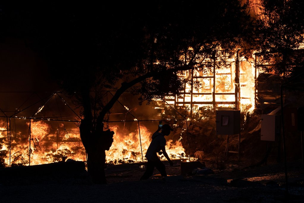 A man runs past burning shelters as a fire burns at the Moria camp on the island of Lesbos, Greece, September 9, 2020. REUTERS/Alkis Konstantinidis