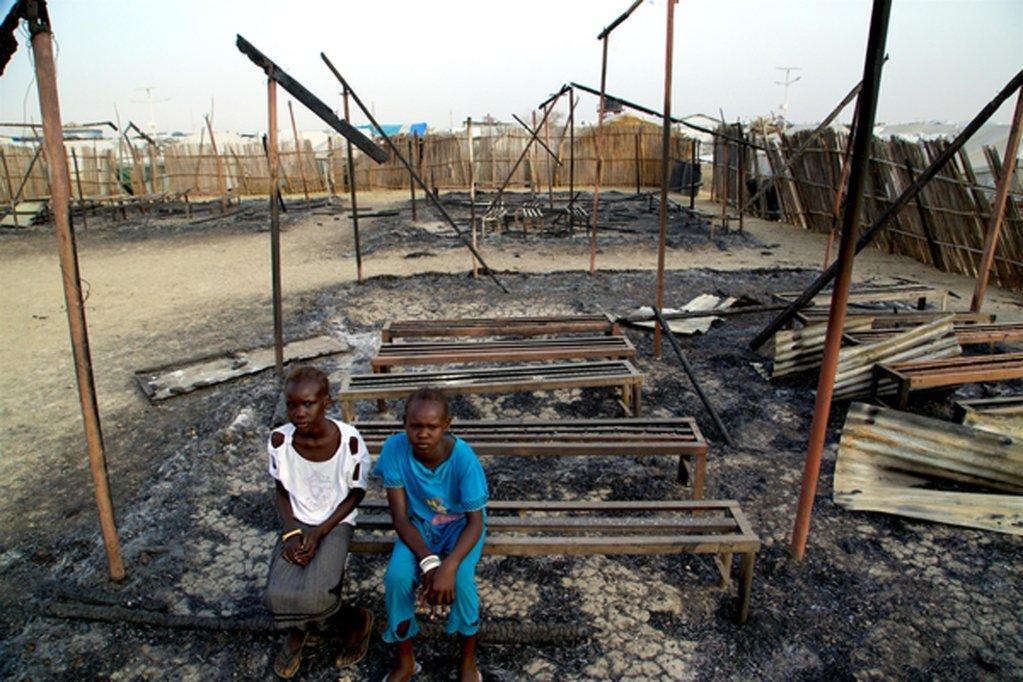 ANSA / طفلان يجلسان بين حطام مدرستهم المحترقة في ملكال بجنوب السودان. المصدر: أنسا/ يونيسف.