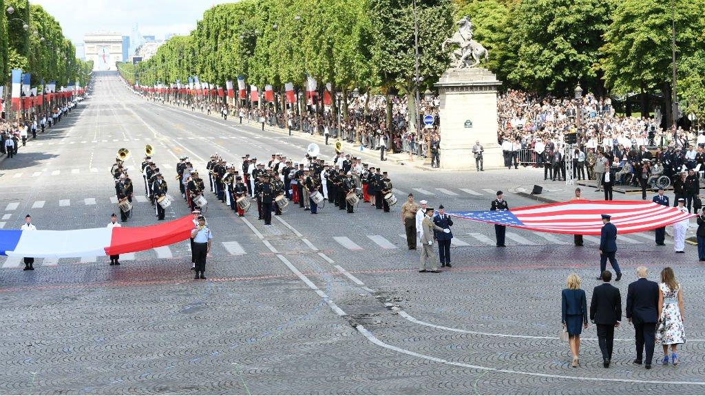 Les présidents français et américain, accompagnés de leurs épouses, devant les drapeaux sur les Champs-Élysées, le 14 juillet 2017. Crédit : AFP
