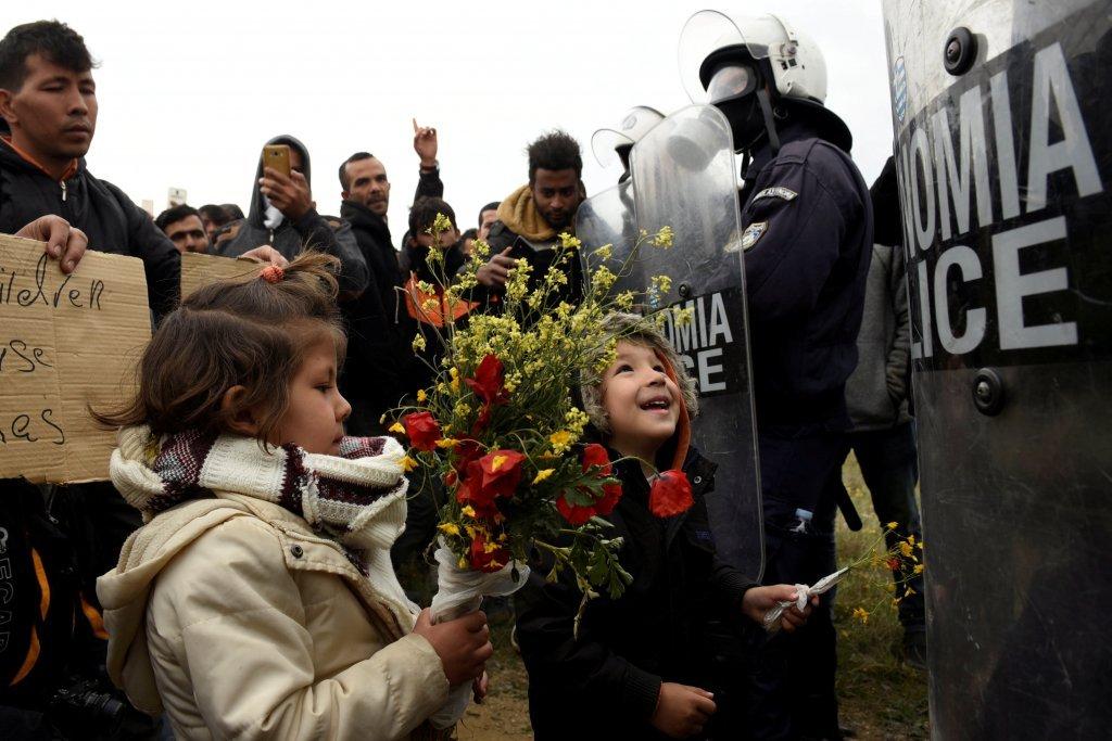Des enfants tendent des fleurs aux policiers grecs, à Diavata, le 6 avril 2019. Crédit : Reuters