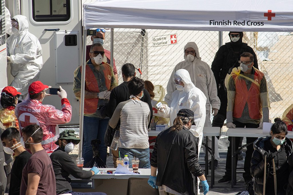 Public health workers check migrants arriving at a new refugee and migrant camp in Greece's Serres region | Photo: N. Economou/picture-alliance