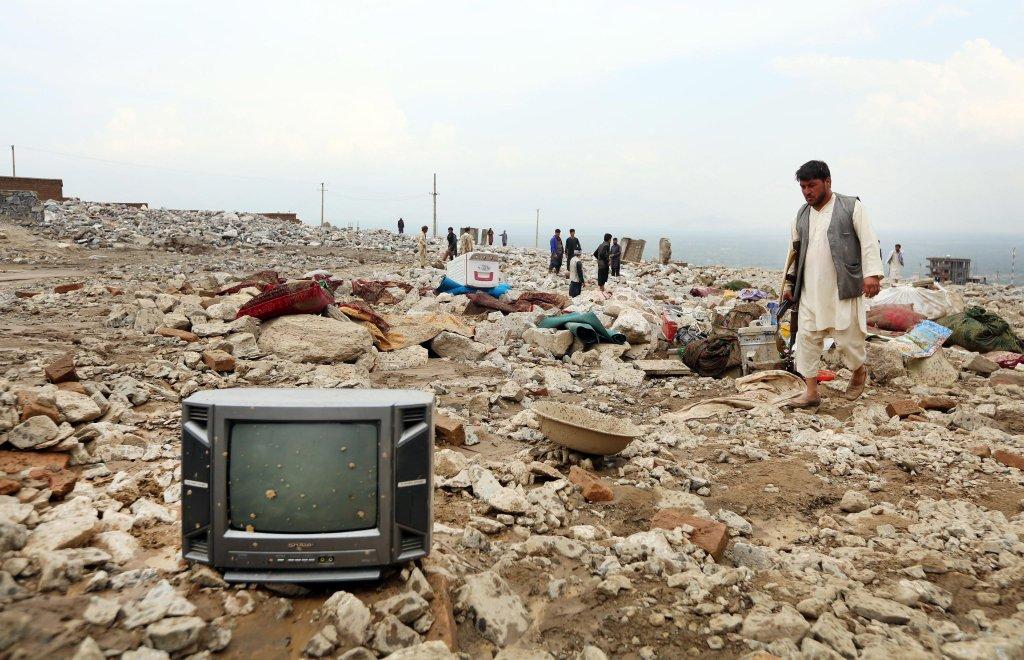 مواطن أفغاني يبحث عن متعلقاته بعد السيول التي اجتاحت مدينة شاريكار الأفغانية. المصدر: إي بي إيه/ جواد جلال.