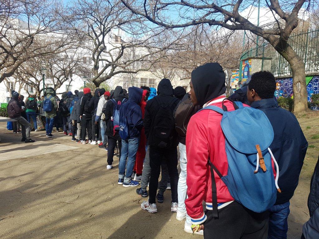 Plusieurs jeunes font la queue pour recevoir un repas chaud au jardin de la rue Pali-Kao, le jeudi 7 mars. Crédit : Maëva Poulet / InfoMigrants.