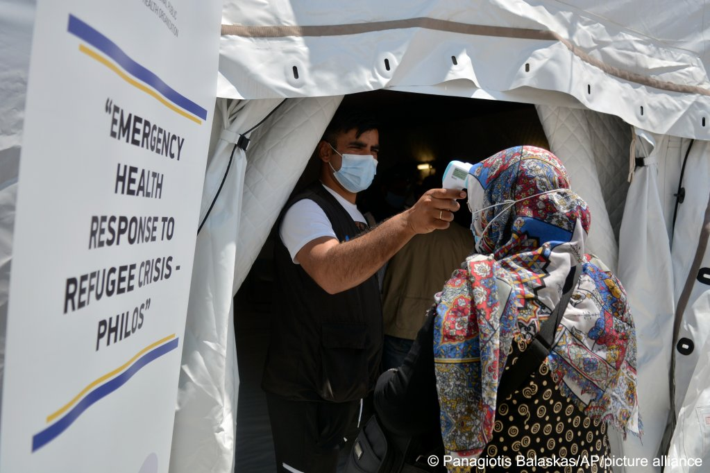 A man takes the temperature of a resident of Kara Tepe refugee camp on the Greek island of Lesbos before she can receive the vaccine against COVID-19 | Photo: Panagiotis Balaskas/AP/picture-alliance