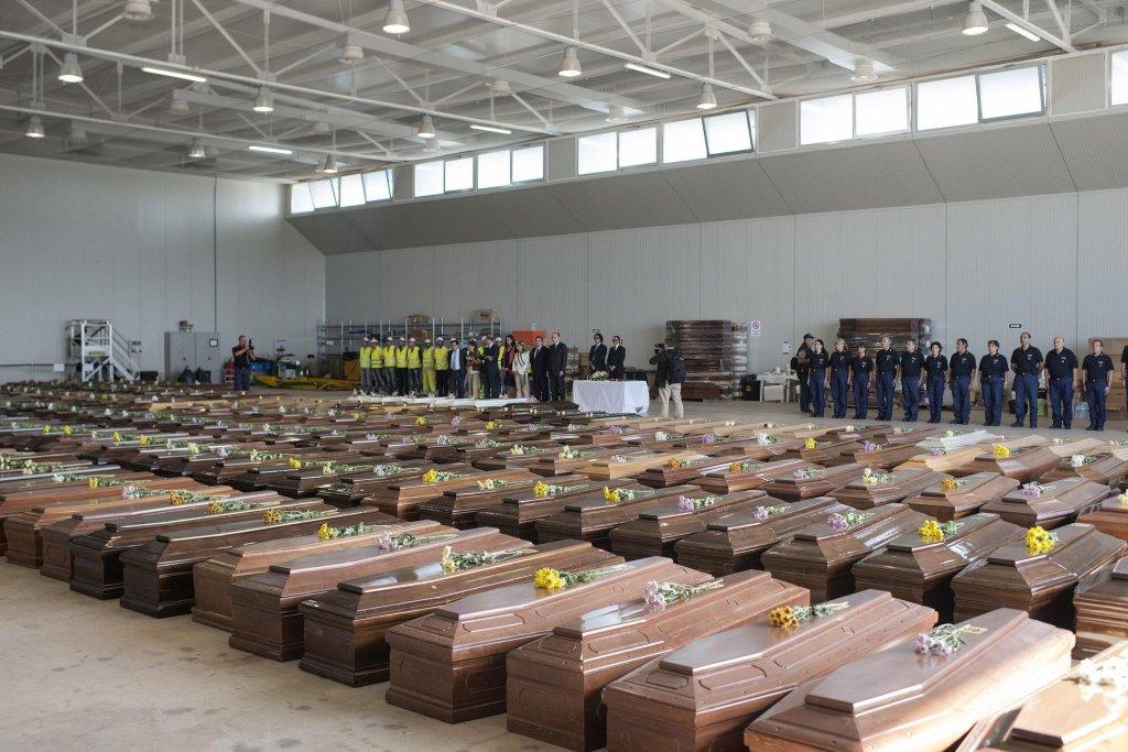 وفود الاتحاد الأوروبي في مطار لامبيدوزا أمام صفوف أكفان ضحايا حادث تحطم سفينة، أودى بحياة أكثر من 300 مهاجر، في تشرين الأول / أكتوبر 2013. المصدر: إي بي إيه/ روبرتو سالوموني.
