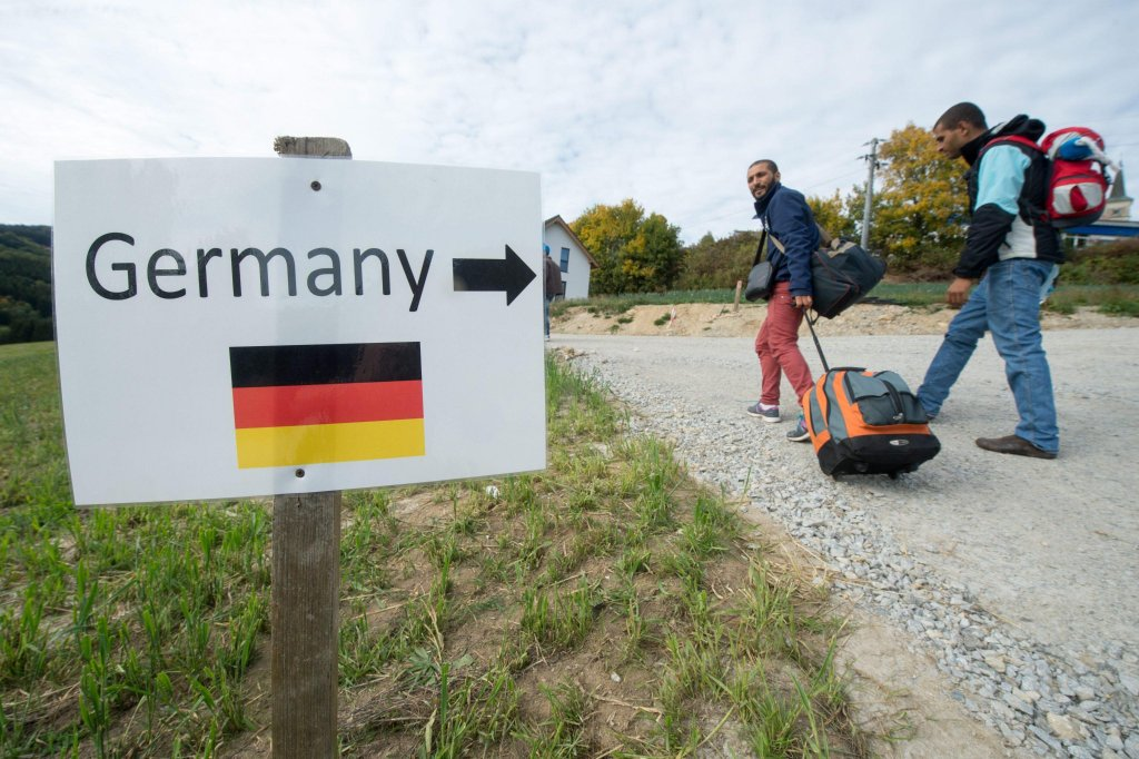 Refugees from Syria walk past a sign that reads 'Germany' and features an images of the German national flag near the Austria-German border in Julbach, Austria Credit: EPA/Armin Weigel