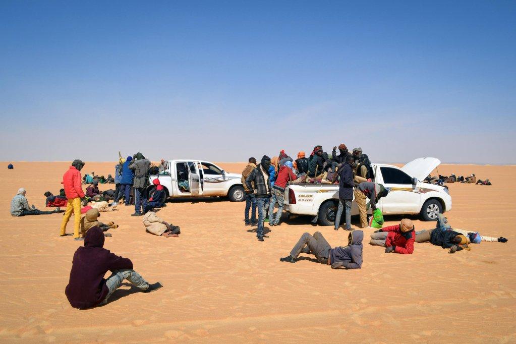 Un groupe de migrants se repose à côté de certains véhicules lors d'une pause de leur voyage à travers le désert de l'Air, au nord du Niger, en route vers la frontière libyenne, le 22 janvier 2019. Crédit : AFP