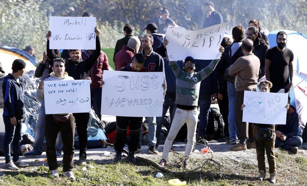 Migrants attempting to cross into Croatia hold banners as they gather near the Maljevac border crossing, Bosnia and Herzegovina   Photo: EPA/Fehim Demir