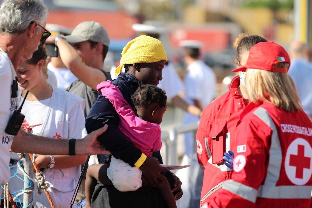 """امرأة وطفلها يهبطان من سفينة أكواريوس التابعة لمنظمة """"أس أو أس ميديتيراني"""" في ميناء باليرمو. المصدر: أنسا/ إيجور بيتيكس."""